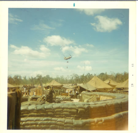 Gela_1969_-_Resupply_chopper_with_mail_and_ammo_each_day.__Carrying_water_trailer._fs